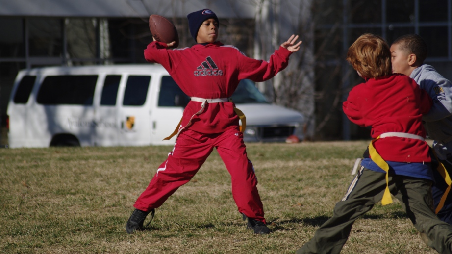 With the ball cocked behind his head, Calvert House Darius Johnson attempts a pass in the 5th-6th grade Flag Football Championship at The Avalon School on December 6, 2012, in Gaithersburg, Md.