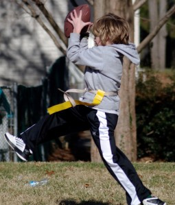 Carroll House fifth grader Riley Smith extends his left leg to stabilize himself after a jump as he completes an  intercepted pass during the Flag Football Championship game on December 6, 2012, at The Avalon School in Gaithersburg, Md.