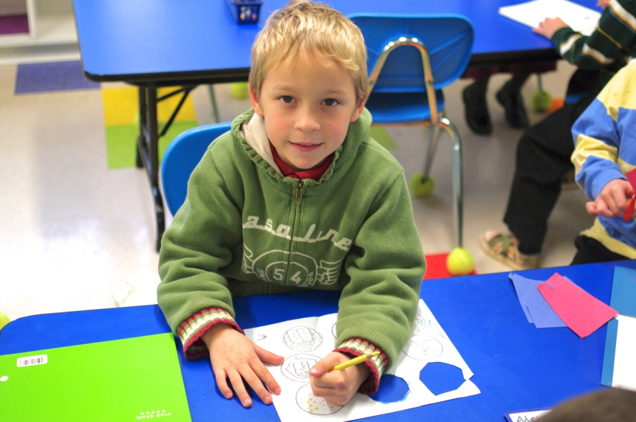 With a colored pencil in his left hand, an Avalon kindergartener colors in pictures on December 17, 2012, in Gaithersburg, Md.