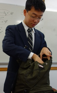 Avalon School Chinese exchange student Tiangao Zhou, a junior, opens a bag he purchased while on a trip to New York City.
