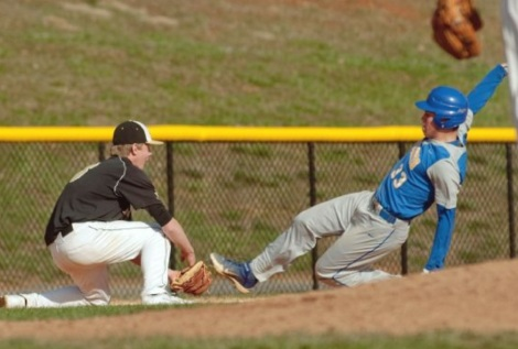 Avalon Black Knights third baseman Pearce Howard extends his glove to tag out a Gaithersburg Trojans base runner in a game at Kelley Park on April 9, 2014, in Gaithersburg, Md.