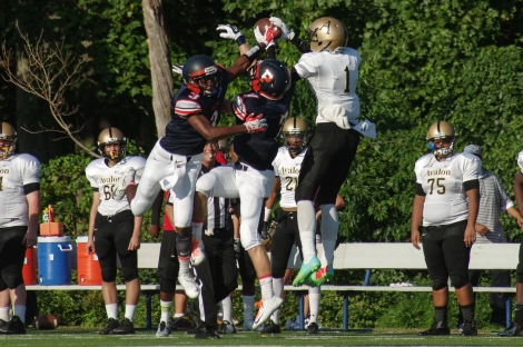 Avalon School wide receiver Treyvon Diggs leaps over two Potomac School defenders to catch a pass during a game on August 29, 2014, in McLean, Va.